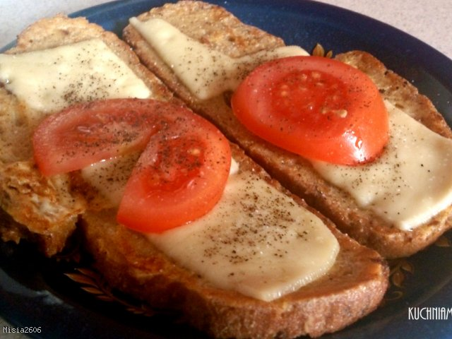 Smażony chleb w jajku i mleku z serem żółtym oraz pomidorem