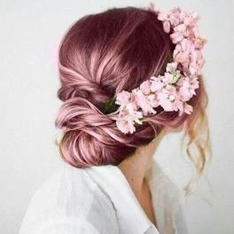 Dziewczyna z metaliczno różowymi włosami z wpiętym w nie wiankiem z kwiatów pozuje odwrócona tyłem na tle białej ściany