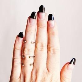 Dłoń na tle szarej ściany z paznokciami ze wzorem half-dip nails i złotymi pierścionkami