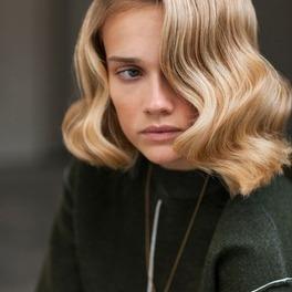 Młoda dziewczyna z blond włosami we fryzurze finger waves