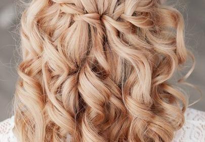 Blond kręcone włosy zaplecione w kaskadowy warkocz