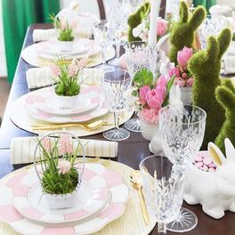 wielkanocna dekoracja na świątecznym stole: kwiaty, króliki, ozdobne serwetki
