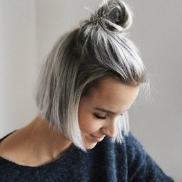 Krótkie szare włosy spięte we fryzurę top knot