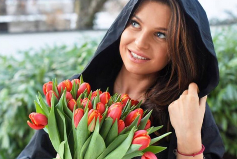 Anna Lewandowska z bukietem tulipanów jaest bardzo szczęśliwa