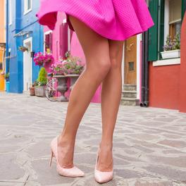 Nogi dziewczyny w beżowych szpilach i różowej rozkloszowanej spódniczce