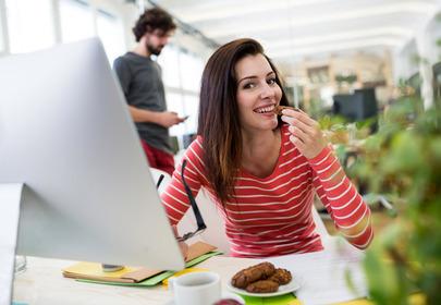 kobieta jedząca przy biurku w pracy