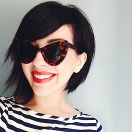 Dziewczyna w czarnych okularach z ciemnymi włosami obciętymi na boba w czarno-białej koszulce w paski uśmiecha się do zdjęcia