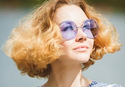Kobieta w niebieskich, okrągłych okularach i granatowej koszulcew białe grochy z krótkimi, puszącymi się, rudymi włosami