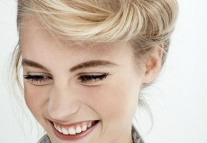 Uśmiechająca się kobieta o blond włosach we fryzurze banana bun