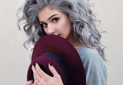 Dziewczyna w szarych kręconych włosach trzyma bordowy kapelusz
