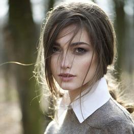 Dziewczyna w związanych włosach w szarym swetrze i białej koszuli