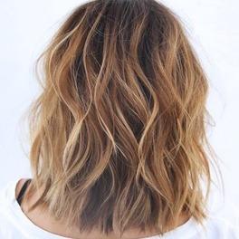 Pofalowane włosy w kolorze ciepłego blondu ścięto do ramion