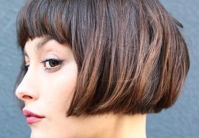 Dziewczyna w brązowych krótkich włosach stoi profilem