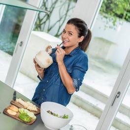 Anna Lewandowska stoi w białej kuchni ubrana w dżinsową koszulę i trzyma w rękach obranego kokosa