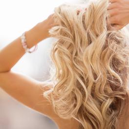 Kobieta odwrócona plecami z rękami uniesionymi ku górze dotyka długich blond kręconych włosów