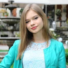 Zdjęcie Julii Wróblewskiej w blond włosach i zielonej kurtce