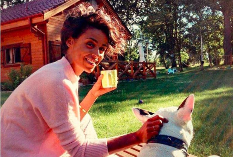 Ola Szwed w długich włosach, ze szklanką w ręce, w różowym swetrze głask psa