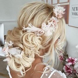 Dziewczyna z długimi blond włosami, spiętymi nad karkiem i ozdobionymi perłami