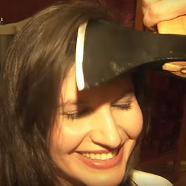 Kobieta z siekierą przy głowie podczas ścinania włosów