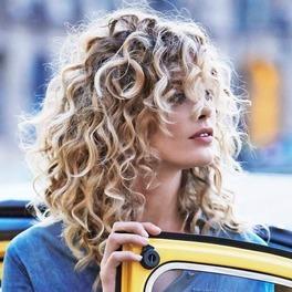 Kobieta w blond kręconych włosach stoi przy taksówce i otwiera drzwi