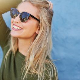 Dziewczyna w okularach przeciwsłonecznych i zielonej bluzce trzyma rękę w blond prostych włosach