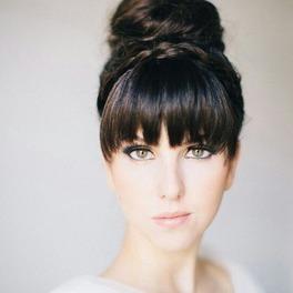 Kobieta w czarnych włosach związanych w kok z grzywką blunt bang