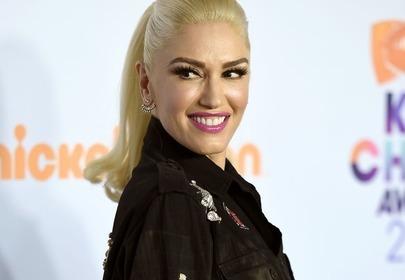 Gwen Stefani w blond włosach związanych w oszukanego uśmiecha pozuje na niebieskim tle w czarnej kurtce