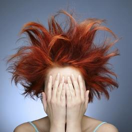 Kobieta z natapirowanymi rudymi włosami zakrywa twarz rękami