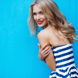 Dziewczyna z długimi blond włosami pozuje na tle niebieskiej ściany w koszulce w biało-czarne paski