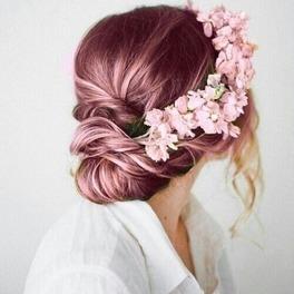 Dziewczyna w różowych włosach z wiankami w białej koszuli siedzi tyłem