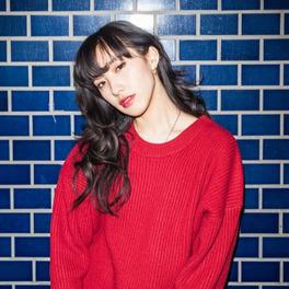 Zdjęcie modelki, która cierpiała na endometriozę. Ubrana jest w czerwony sweter i stoi na tle niebieskiej ściany