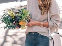 Dziewczyna z długimi włosami w dżinsach i szarym swetrze i z beżową torebką, trzyma w dłoniach bukiet kwiatów