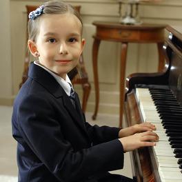 Mała Emilka Kowalska siedzi przy fortepianie