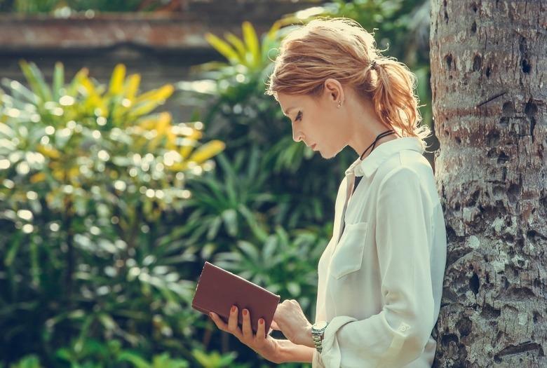 dziewczyna z książką opiera się o drzewo