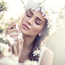 Kobieta z wiankiem w brązowych włosach na tle kwiatów wącha perfumy