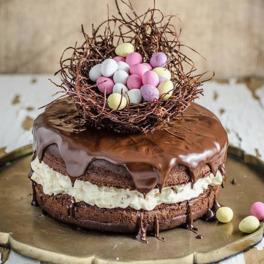 smakowite ciasto oblane czekoladą z ozdobnymi jajkami na wierzchu