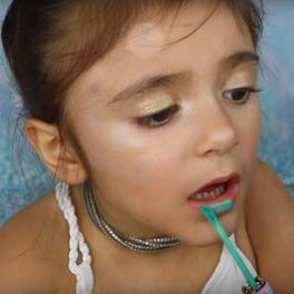 mała dziewczynka maluje się profesjonalnymi komstykami do makijażu