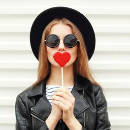 Dziewczyna w czarnym kapeluszu, czarnej kurtce i koszulce w paski trzyma czerwonego lizaka w kształcie serca przy ustach