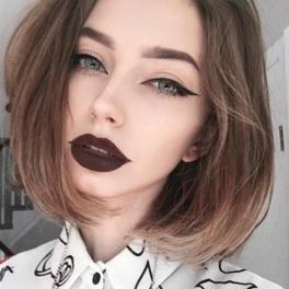 dziewczyna z kreską na powiekach i ciemną szminką w białej koszuli