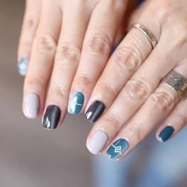 Dłonie z paznokciami w kształcie kwadratów z manicure w kolorze lazurowym i czarnym