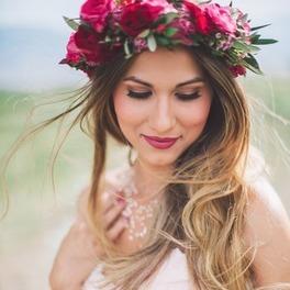 Dziewczyna z blond długimi włosami i wiankiem z czerwonych kwiatów na głowie siedzi patrzy w dół ubrana w białą sukienkę