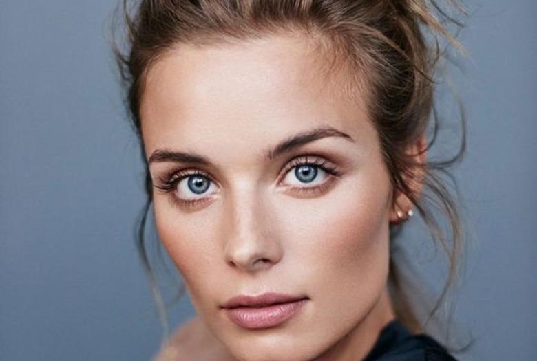 Dziewczyna z blond włosami i niebieskimi oczami pozuje w czarnej koszulce na szarym tle
