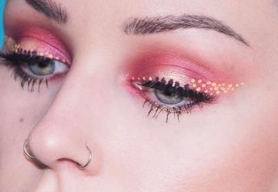 Twarz kobiety z bliska która ma makijaż w kolorach różu i brzoskwini oraz namalowaną na powiekach jaskółkę z kolorowych kropek
