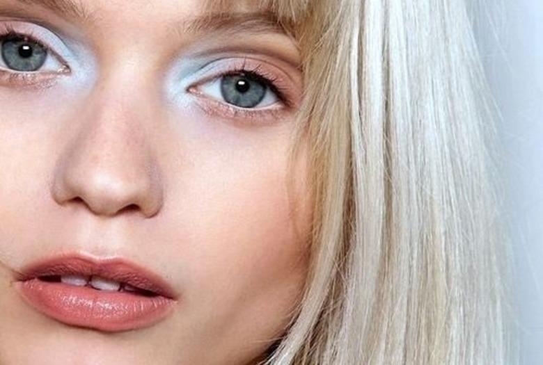 Dziewczny a zbardzo jasnymi blond włosami i niebieskim makijażem