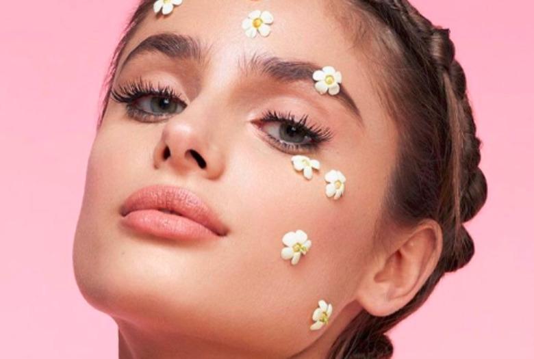 Dziewczyna z naklejkami w kształcie kwiatków na twarzy