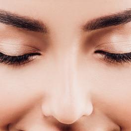 Twarz kobiety z zamkniętymi oczami i długimi rzęsami z bliska