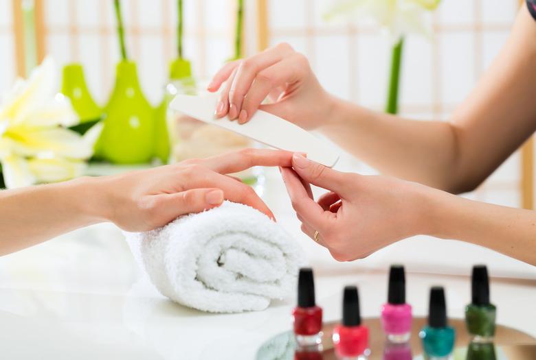 Dłoń i lakiery w trakcie wykonywania manicure