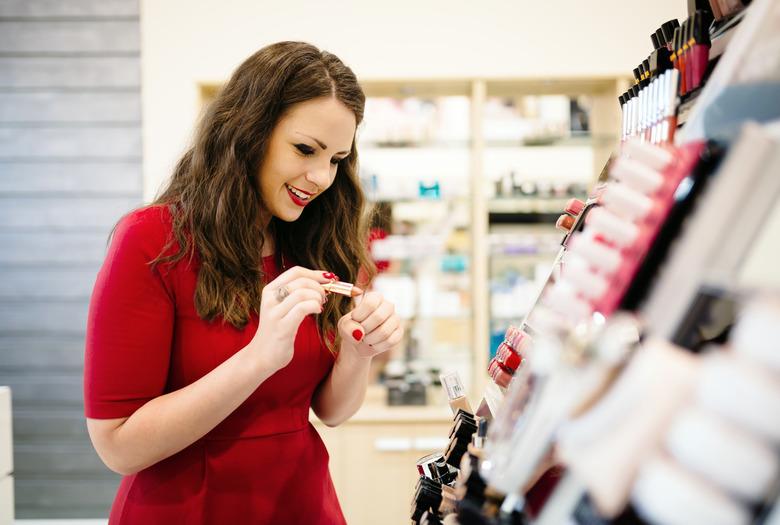kobieta w drogerii w czerwonej sukience testuje szminkę do ust