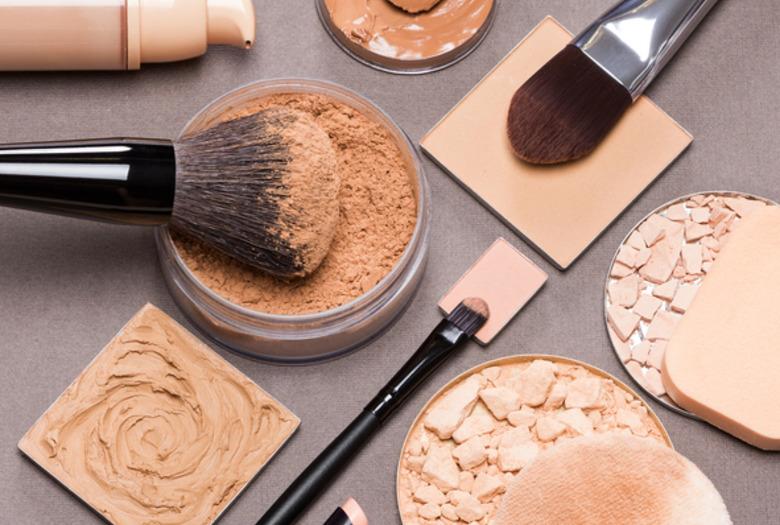 Rozrzucone kosmetyki do makijażu twarzy z położonymi na nich pędzlami