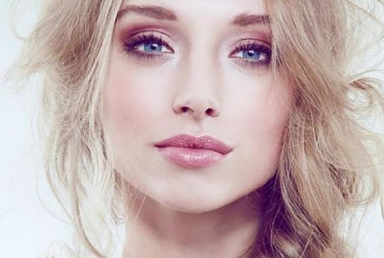 Blondynka z włosami zaplecionymi w luźnego warkocza w delikatnym makijażu podkreślającym niebieskie oczy